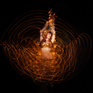 Spiral Orchid fusion belly dancer with LED Isis wings in motion on extended exposure