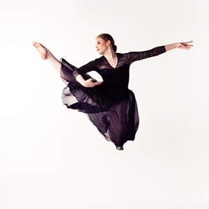 Musical Theatre performer Amelia performing a jump with one leg tucked.