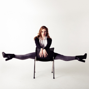 Musical Theatre performer Amelia looking formidable while doing the splits sitting backwards on a chair.