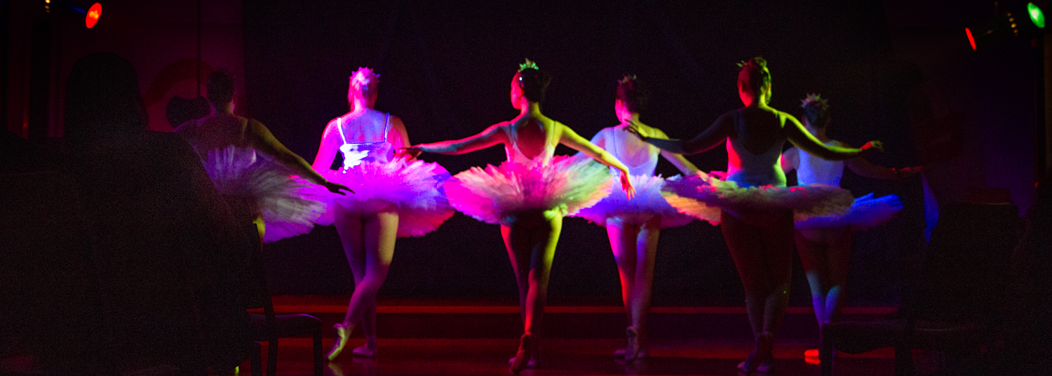 ballet dancers in a row facing the back with rainbow stage lights