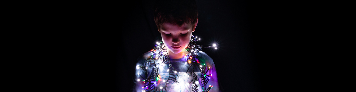a young boy in the dark with fairy lights draped around his shoulders casting their glow on his face
