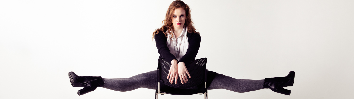Theatre performer Amelia Burton sitting backwards on a chair doing the splits.